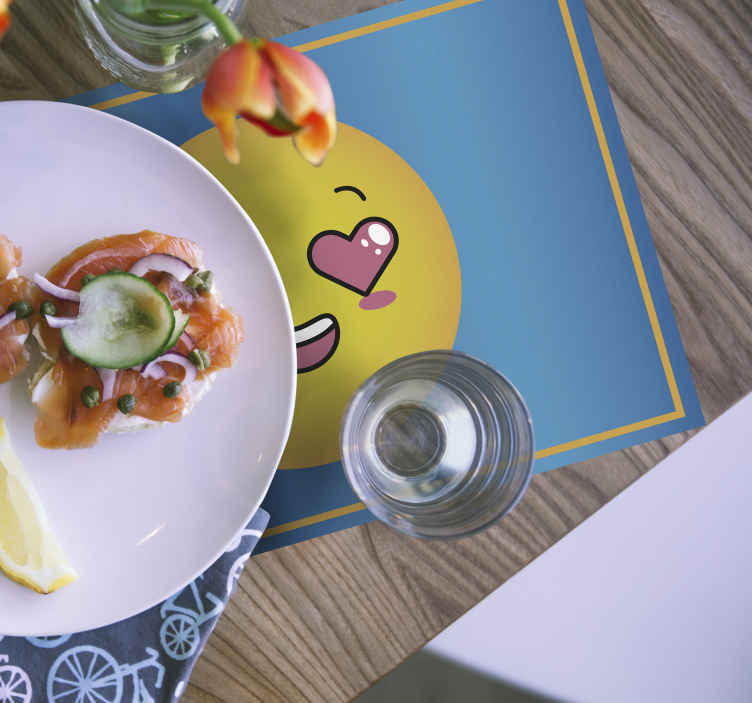 TenStickers. Heart eyes emoji kids table mat. Adorable emoji placemat which features a heart eyes emoji blushing on a stunning blue background. Extremely long-lasting material.