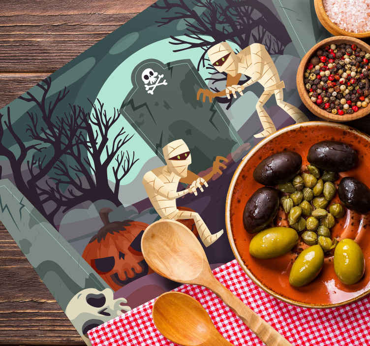 TenStickers. Scary Mummies Halloween table mats. This Halloween placemat features a scary graveyard with misty cartoon trees and a large tombstone in the middle. Discounts available.