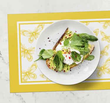 Un'elegante tovaglietta da tavola in vinile per la casa e il ristorante. è caratterizzato da uno sfondo giallo con diverse farfalle.