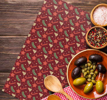 A red coloured place-mat with design of Christmas candy, stars, ornamental leafs and bells. It is original and made with high quality material.