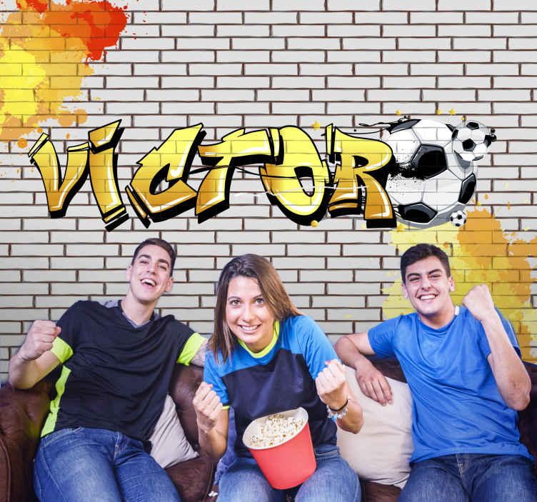 TenStickers. Nogometni grafiti personalizirani zidni zid. Grafiti zidni zid na kojem se nalazi ime vašeg djeteta napisano fontom grafita uz sliku nogometne lopte uz njega. Lako se nanosi.