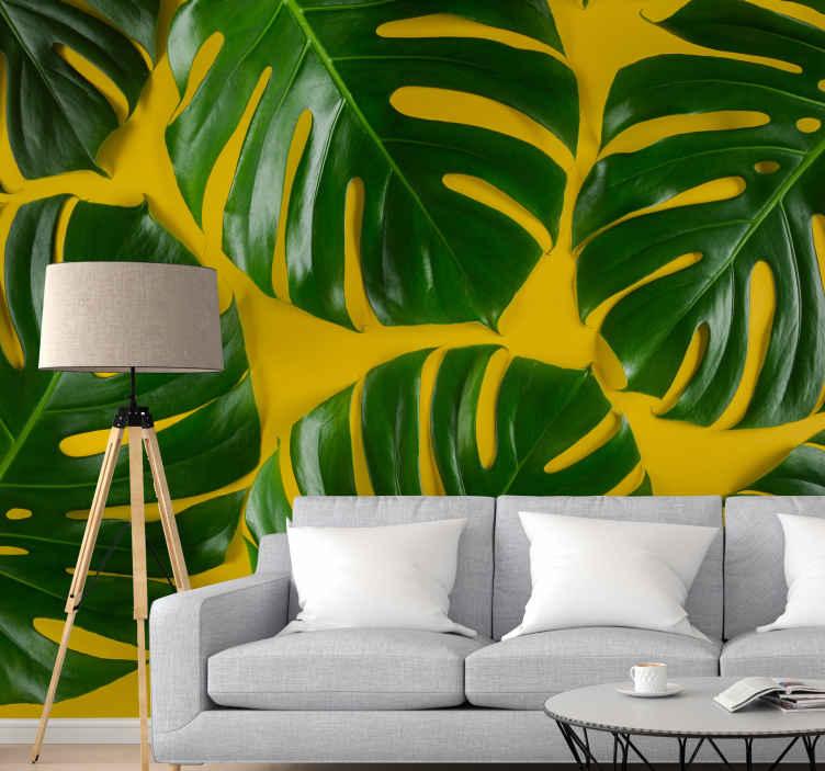 TenStickers. Zelena in rumena stenska stena monstera. Polna orjaških, zelenih pošastov, vas bo na krepko rumenem ozadju stenska slika približala naravi! Na voljo za dostavo na dom.