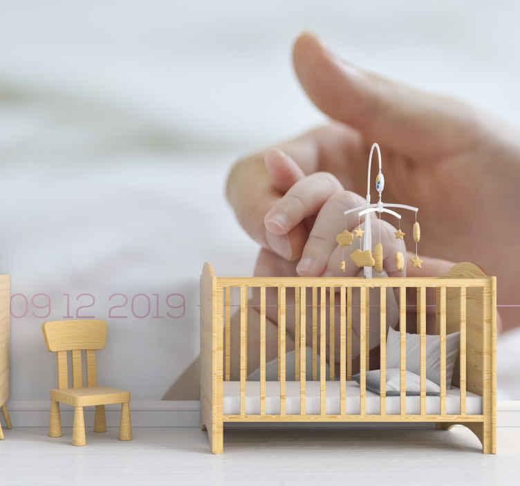 TenStickers. Fotomurais de Parede Bebê e adulto de mãos dadas. fotomural vinílico personalizável da foto do quarto do berçário da data de nascimento do bebê exibindo a imagem de uma mão de adulto segurando a mão de um bebê.