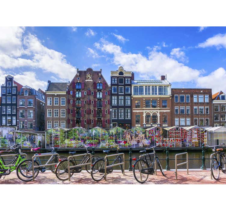 TenStickers. Bloemenmarkt Amsterdam muurschildering behang. Dit stadsfotobehang toont de prachtige bloemenmarkt naast een gracht in amsterdam de felle kleuren van deze foto zullen een geweldige decoratie zijn!