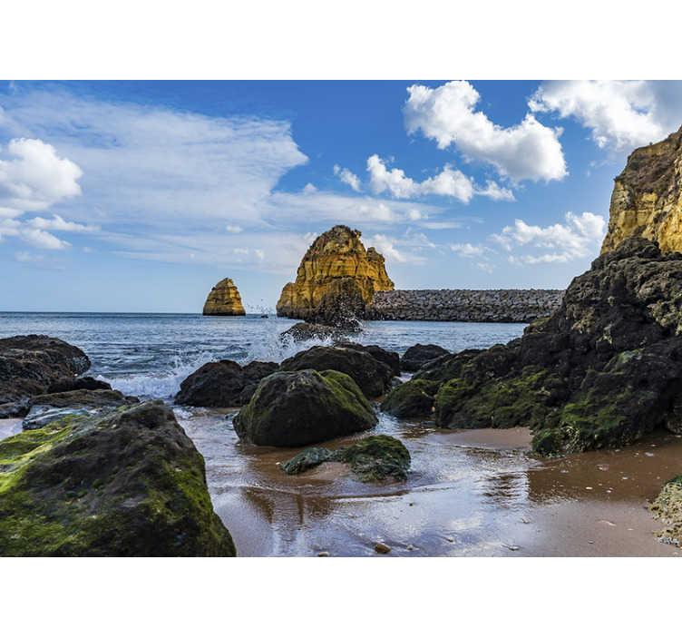 TenStickers. Mural de parede de mar nublado falésias. Este fotomural de parede de mar mostra uma praia portuguesa com altas falésias ao fundo e ondas quebrando nas rochas com um céu nublado como pano de fundo.