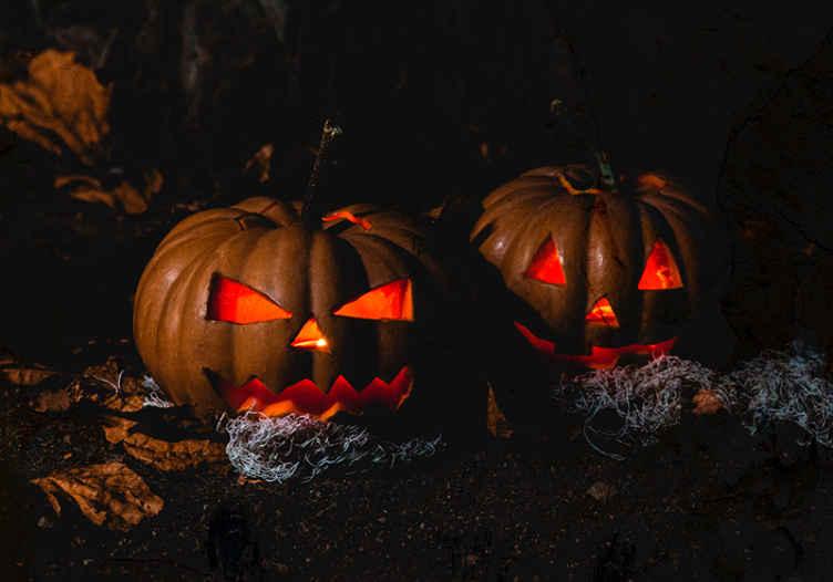 TenStickers. Fototapete Wand Schwarzer Hintergrund mit einem kürbis halloween. Schwarzer Hintergrund mit gruseligem kürbis-wandbild. Ein entwurf eines zwei großen gruselig geschnitzten kürbises mit rotem licht, das von innen emittiert wird.