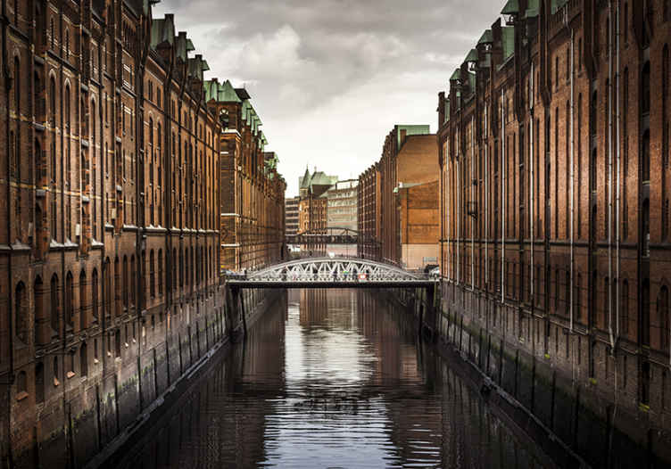 TenStickers. Kanal sa mosta zidne tapete. Country krajolik pogled zidni zid. Sjednite u svoju dnevnu sobu samo uživajući u ovom pogledu na kanal koji prolazi kroz razne građevinske strukture.