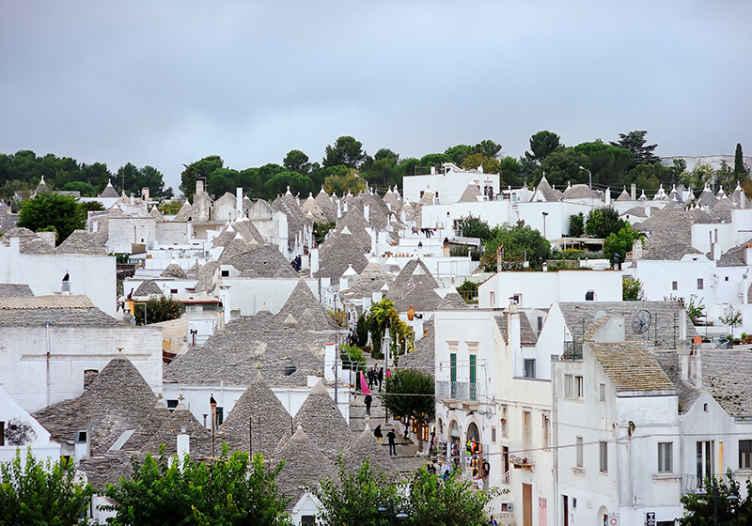 TenStickers. Tapisserie salon Alberobello trulli. Papier peint du salon qui présente une belle image du village d'alberobello, en italie et des superbes maisons de trulli qui s'y trouvent.