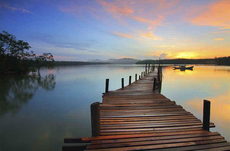 TenStickers. Palube do oceanskih i nebeskih krajolika. Zašto ne biste kupili ovaj nevjerojatni zidni zid s drvenim mostom za prijelaz. Predstavlja prekrasno plavo nebo sa zatvaranjem zalaska sunca.