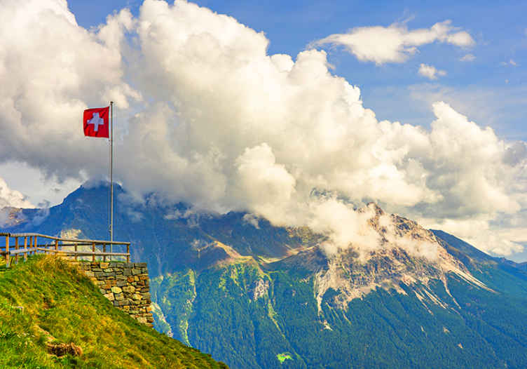 TenVinilo. Fotomural paisaje de Suiza con bandera. Amas suiza, amas los paisajes, entonces este fotomural paisaje de Suiza con bandera. Diseño con montañas ideal para tu salón ¡Envío gratuito!