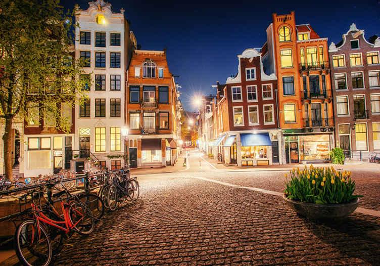 TenStickers. Amsterdam zidni zid s pogledom na grad. Pogledajte njegov prekrasni zidni motiv inspiriran ulicom u amsterdamu s tradicionalnim holandskim zgradama i biciklima. Kućna dostava!