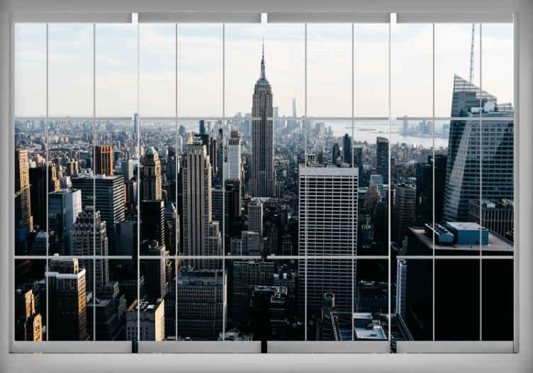 TenVinilo. Fotomural New York Ventana en nueva york. Un hermoso fotomural de nueva york con innumerables luces y edificios. . Los adhesivos de pared de nueva york modernizarán cada lugar de su hogar.