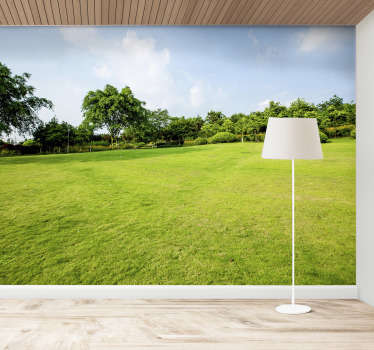 This scenery photo mural shows a beatiful green meadow with trees in the background The bright colors of this image are stunning and will impress!