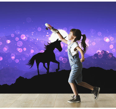 This beautiful photo wall mural shows the black silhouette of a unicorn and glitter and purple mountains in the background.