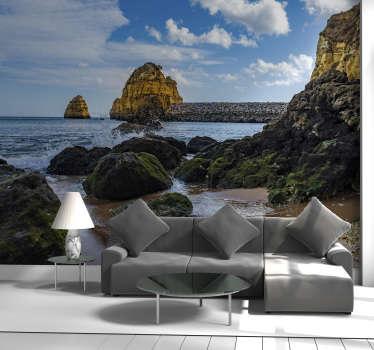 Este fotomural de parede de mar mostra uma praia portuguesa com altas falésias ao fundo e ondas quebrando nas rochas com um céu nublado como pano de fundo.