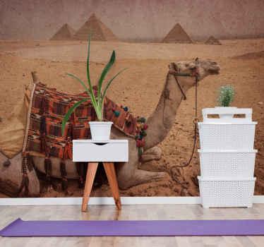 верблюд спит перед фреской в виде пирамиды. верблюд с монтажным стулом и пирамиды деревьев на заднем плане. получите с немедленной доставкой!