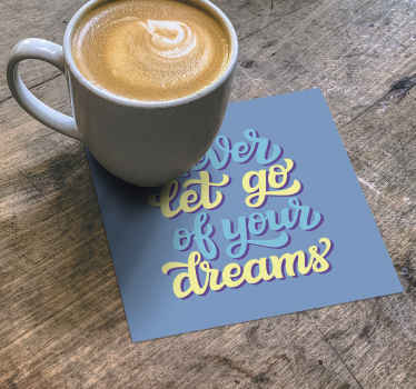 'Never let go of your dreams'' drink coaster text.  The design is made on a plain blue background with a blue and yellow colored text .