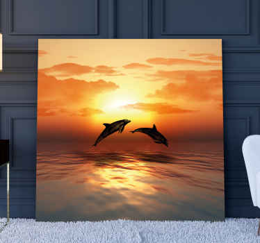 Canvas print with dolphins. The animals are jumbing over water surface during a sunfall. Easy to hang on a wall or place freely on a desk.