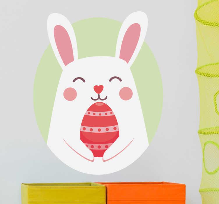 TenVinilo. Pegatinas infantiles conejo de pascua. Vinilos Pascua que muestran la ilustración de un roedor de orejas alargadas portando un huevo en tonos rojizos.