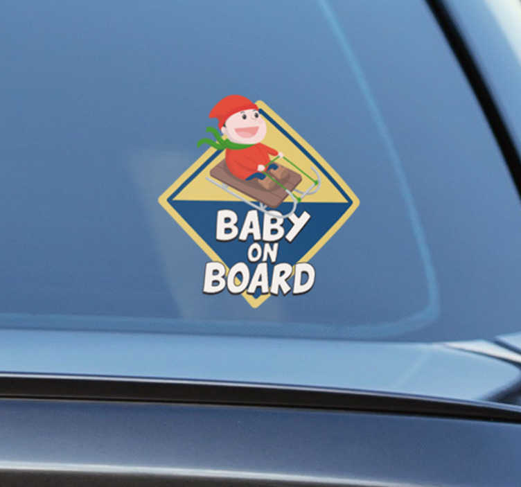 TenStickers. Adesivo slitta baby on board. Adesivo per auto natalizio con la scritta baby on board raffigurante un bambino vestito con i tipici colori natalizi rosso e verde su di una slitta.