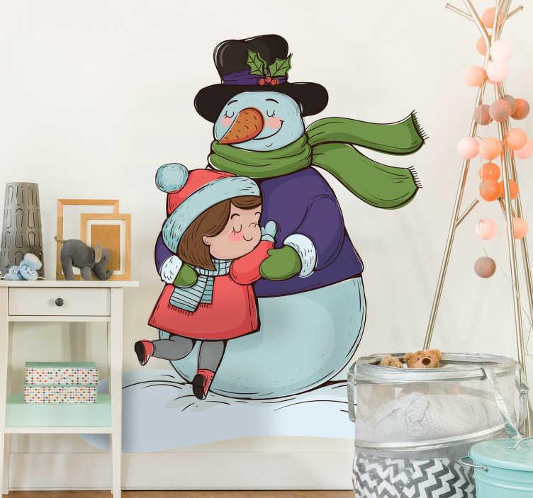 TenVinilo. Vinilo infantil abrazo navideño. Vinilos decorativos Navidad con el dibujo de una niña y un típico muñeco de nieve abrazándose.