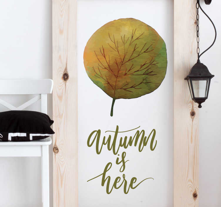 """TenVinilo. Vinilos otoño autumn is here. Vinilos decorativos otoño con el perfil de una hoja de árbol y el texto en inglés """"el otoño está aquí""""."""