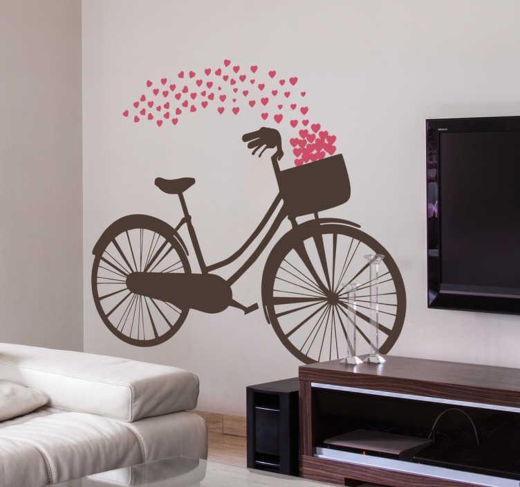 TenStickers. Muursticker fiets met hartjes. Een leuke muursticker met een fiets waar hartjes uit de fietsmand komen. Fleurig en stijlvol, geschikt voor allerlei interieurstijlen.