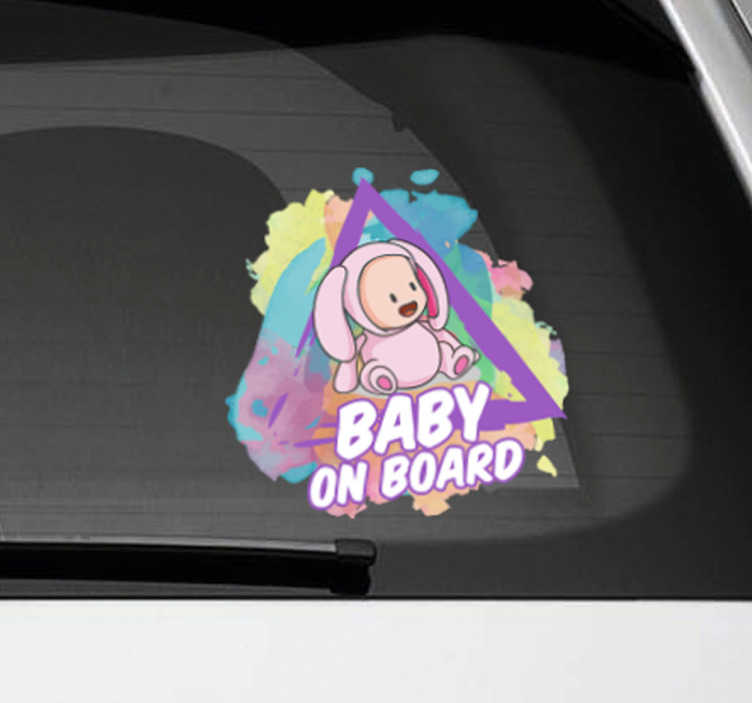 Tenstickers. Roiskemaali autotarra baby on board. Roiskemaali autotarra baby on board. Baby on board tarra autoon, jossa on suloinen vauva pupu-asussa ja taustalla värikkäitä maaliroiskeita.