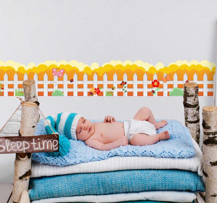 TenVinilo. Cenefa infantil valla con flores. Cenefa adhesiva para cuarto infantil con el dibujo de unas vallas de madera blancas, detrás un fondo de nubes anaranjadas.