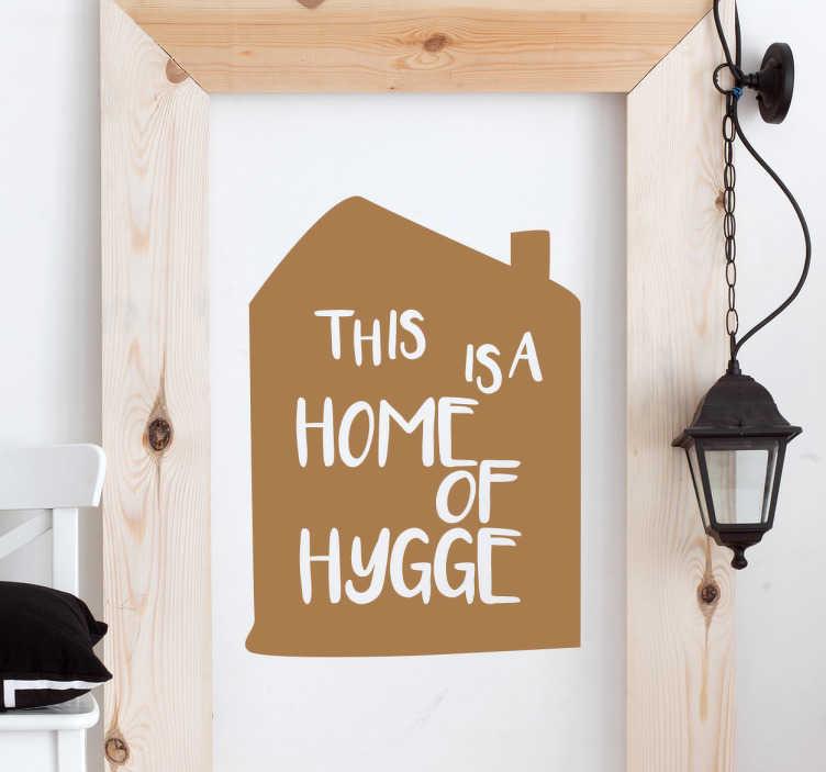 """TenStickers. Engelsk hygge sticker. Dekorativt sticker med teksten """"This is a home of hygge"""". Os danskere ved hvad det vil sige at have et hyggeligt hjem, og vigtigheden ved det."""