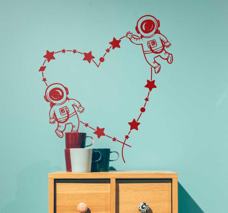TenStickers. Muursticker astronauten liefde. Originele muursticker met een illustratie van twee astronauten die rond de kosmos cirkelen en een sterrenbeeld in de vorm van een hart tekenen.