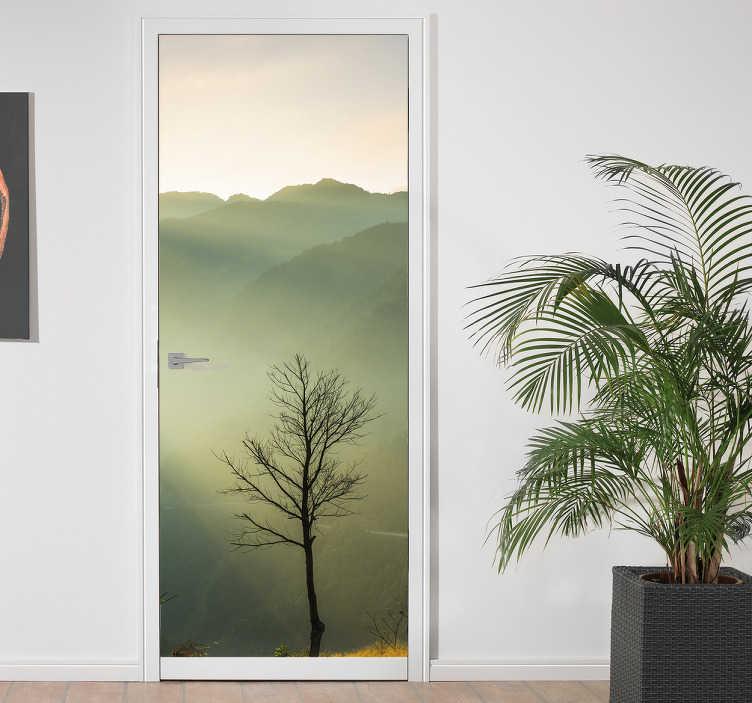 Tenstickers. Sumuinen maisema ovitarra. Upea ja tyylikäs ovitarra sumuisella kukkulamaisemalla jossa auringonsäteet kohtaavat puun. Tällä tarralla muutat tylsänkin oven portiksi satumaiseen maailmaan.