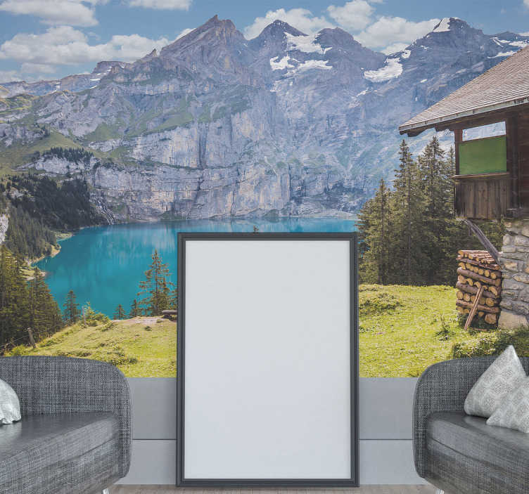 TenVinilo. Vinilo montaña paisaje. Vinilo fotomural con  un fotografía de una casa con vistas a un cristalino lago y a un escarpada cordillera.