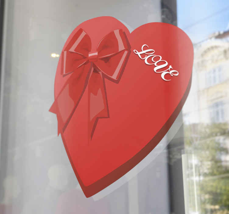 """TenStickers. Sticker Valentijnsdag doos pralines. Een romantische muursticker van een doos bonbons in de vorm van een hartje met de tekst """"love"""" en een leuk rood strikje."""