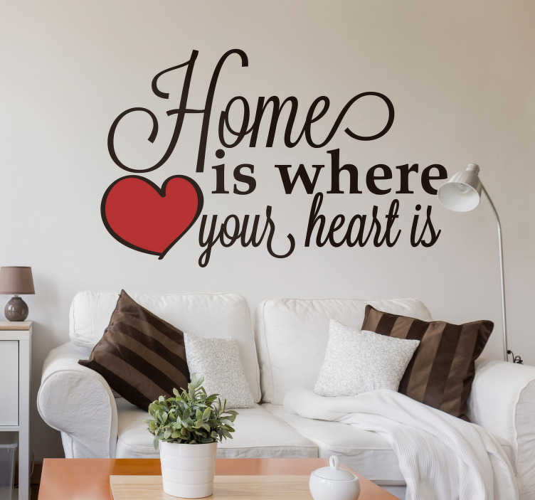 TenStickers. Home is where the heart is sticker. De tekst 'home is where the heart is' is geschreven in zwierige letters met een rood hart om het af te maken. Deze tekststicker past  in de woonkamer.