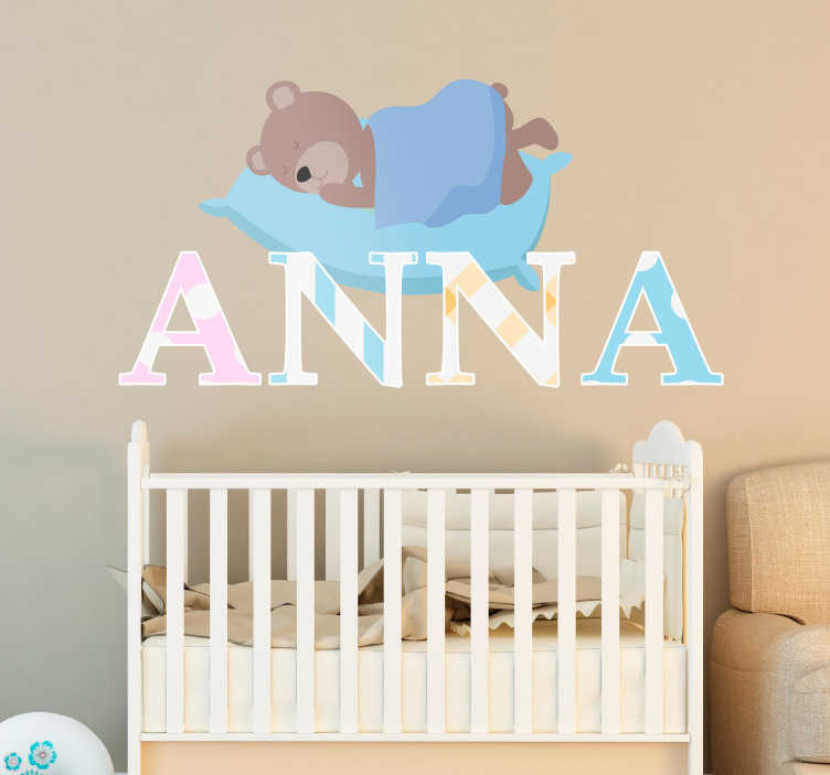 TenStickers. Naamsticker slapende knuffelbeer. Decoreer de babykamer met deze naamsticker. De sticker heeft een afbeelding van een slapende knuffelbeer op een kussen. Onder de beer kunt u zelf de naam aangeven.