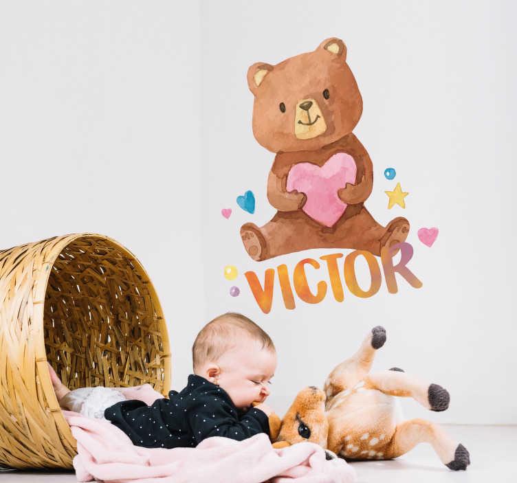 TenStickers. Autocolantes para casa peluche com coração. Um ursinho fofo a agarrar num coração cor-de-rosa com um nome que pode ser personalizado por baixo.