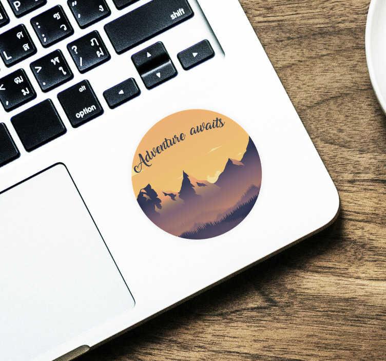 """TenStickers. Naklejka na laptopa """"Adventure awaits"""". Naklejka na laptopa z napisem """"Adventure awaits"""" i pięknym zarysem gór na tle wschodzącego słońca. Nasi graficy pomogą Ci z projektem!"""