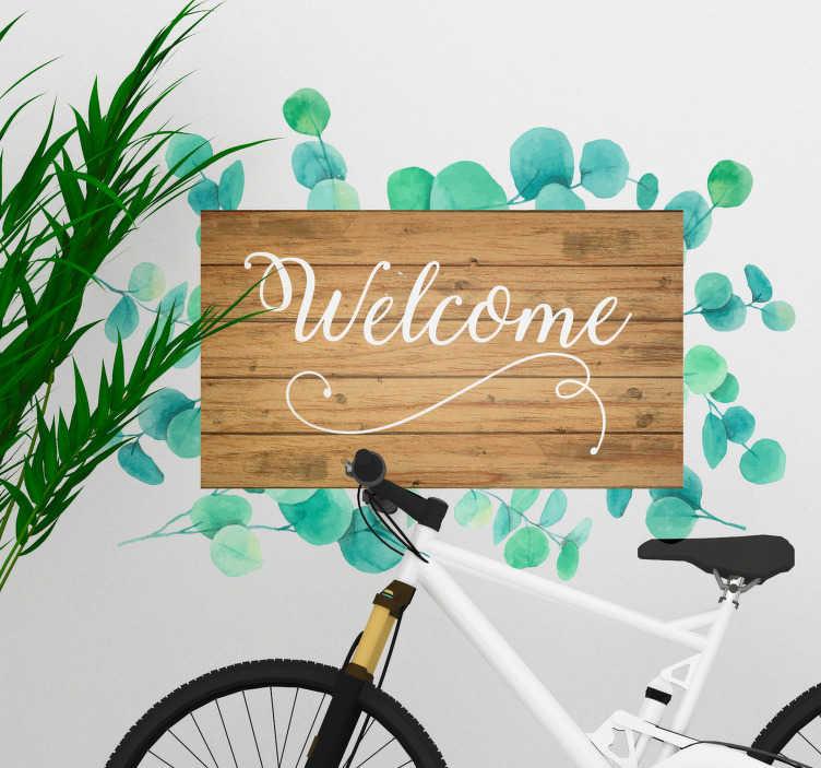 """TenVinilo. Vinilo frase eucalipto texto welcome. Original pegatina adhesiva formada por el texto """"Welcome"""" sobre una lámina de madera con hojas de eucalipto a su alrededor. +50 Colores Disponibles."""
