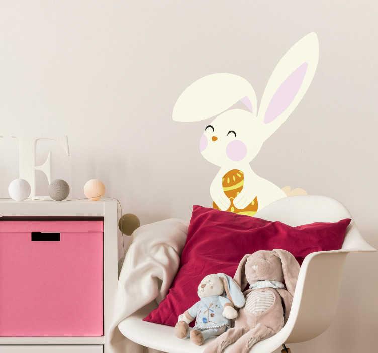 TenVinilo. Vinilo pared conejo de Pascua con huevo. Pegatina adhesiva para habitación infantil o escaparate formada por un conejito sujetando un huevo de Pascua. Fácil aplicación y sin burbujas.