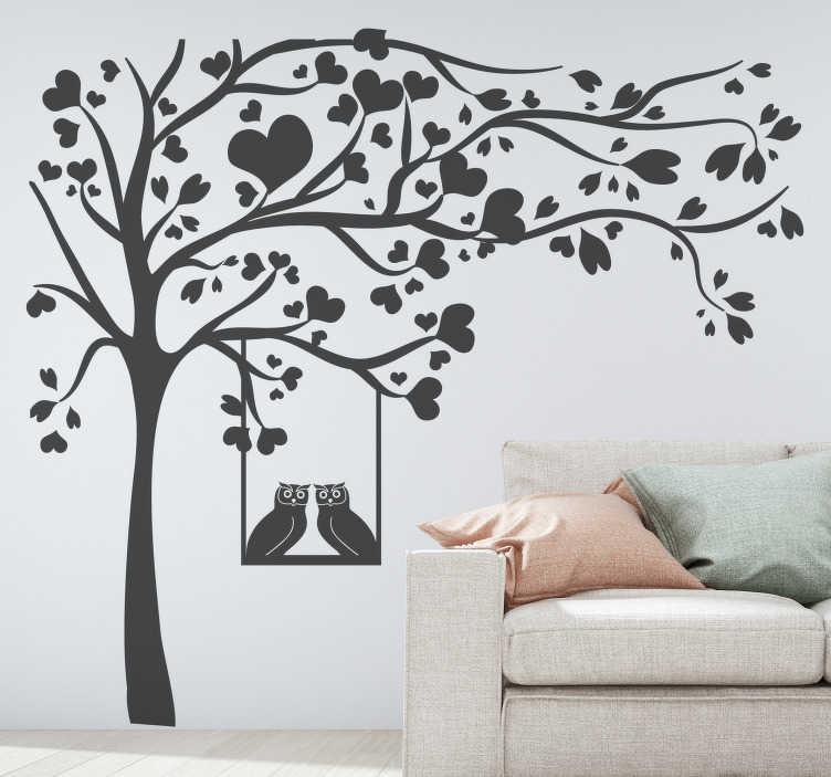TenStickers. Baum mit Herzen Wandtattoo. Dekorativer wandwandaufkleber eines baumes mit gut ausgebreiteten zweigen mit zwei daran hängenden eulen. Erhältlich in monofarboptionen.