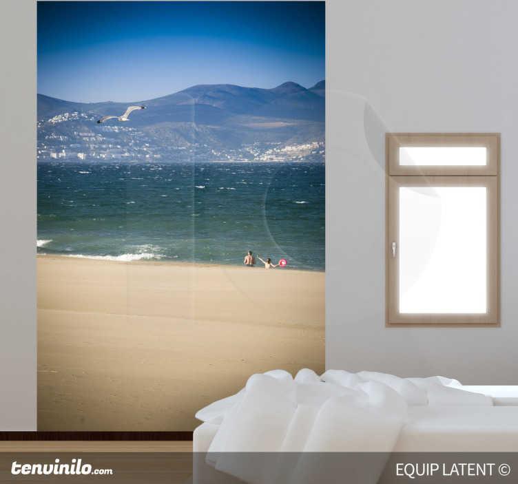TenStickers. Sticker decorativo spiaggia ventosa. Fotomurale d'autore che ritrae una spiaggia sabbiosa con il mare di fronte e le montagne sullo sfondo. Una fotografia originale di Latent Estudi.