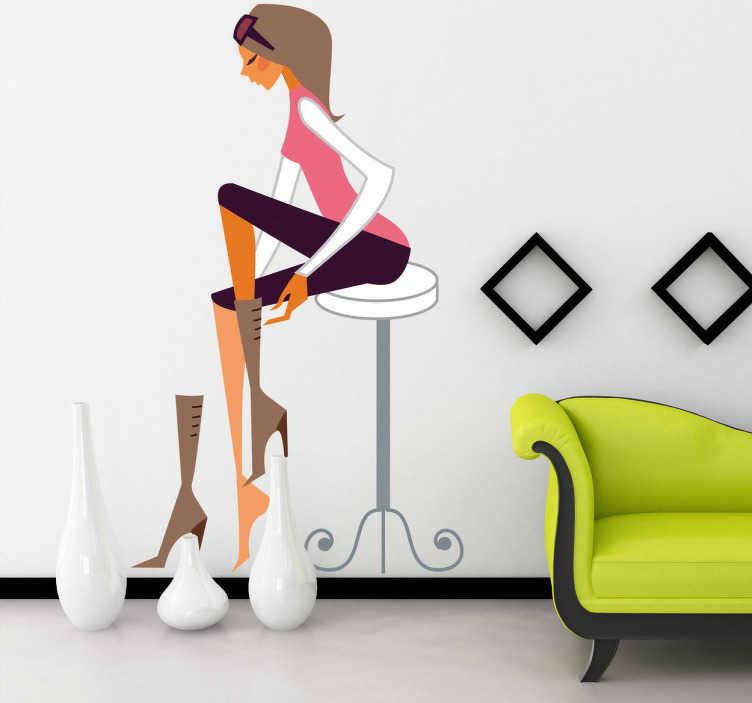 TenVinilo. Vinilo decorativo chica probando calzado. Adhesivo de una mujer sentada sobre un taburete probándose unas elegantes botas de fino tacón. Decoración para tu salón llena de glamour.