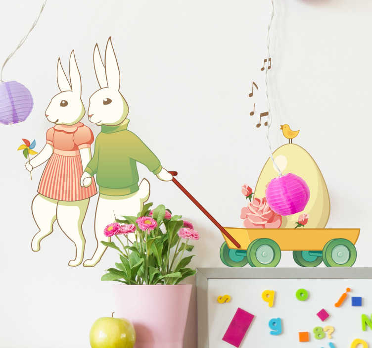 TenStickers. Adesivo infantil par de coelhos da páscoa. Vinil decorativo com uma ilustração de coelhos da páscoa apaixonados que vão a arrastar um carrinho com um grande ovo.