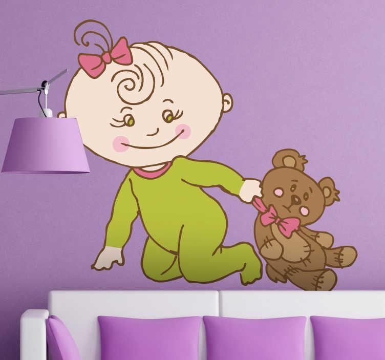 TenStickers. Sticker kinderkamer baby met knuffelbeer. Een mooie wandsticker van een baby met een groen kruippakje en een roze strikje in haar haren dat met haar teddybeer speelt.