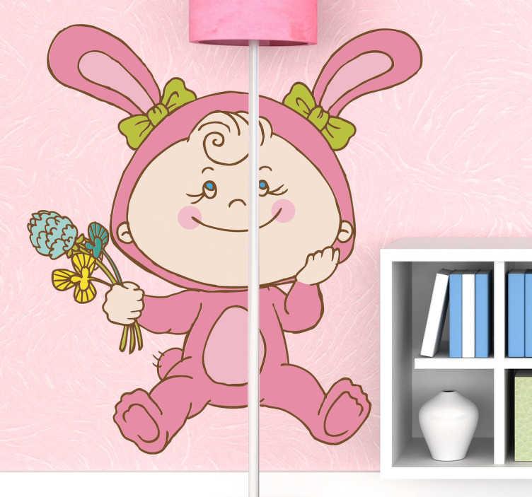 TenStickers. Kindje in konijnenkostuum pasen sticker. Kinderen muursticker met een klein kindje dat gekleed is in een roze konijnen kostuum met bloemen in haar hand!
