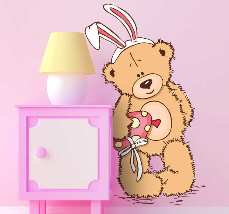 TenStickers. Sticker kinderen knuffelbeer. Een leuke wandsticker van een schattige teddybeer met een hartje in het midden van zijn buik en vermomd met konijnen oren.