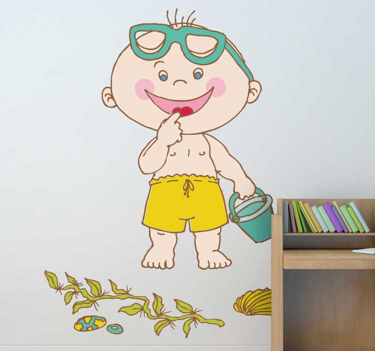 TenStickers. Sticker kinderkamer peuter strand. Muursticker van een vrolijke kleuter met een gele zwembroek en een emmertje op het strand. Mooie wanddecoratie voor de versiering van de babykamer.