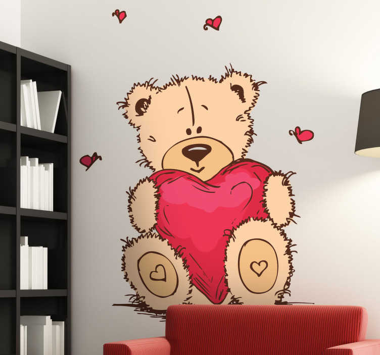 TenStickers. Sticker kinderkamer knuffelbeer met hartje. Een prachtige muursticker van een beige knuffelbeer met een roze hartje vast en rond de teddybeer zie je roze vlinders in de vorm van een hartje.
