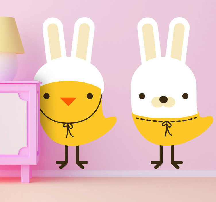 TenStickers. Sticker kinderkamer kuikens konijn. Een leuke en grappige muursticker van 2 kuikens, één kuiken heeft een hoed met konijnen oren aan en de andere heet een konijnenmasker aan.